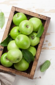 Green apples in wooden box